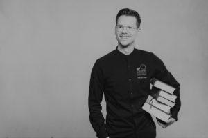 Niko Rittenau lächelt mit einem Stapel dicker Bücher unter dem Arm