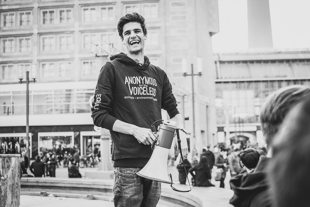 Valentin Zech lacht mit einem Megaphone und trägt eine Anonymous for the Voiceless Hoodie