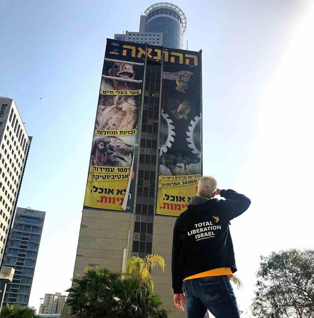 Nir Rosenfeld in Israel vor einem Hochhaus mit einem Plakat, dass die Tierindustrie anprangert.